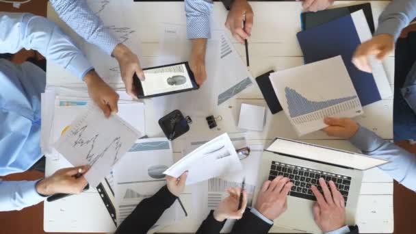 Nejlepší pohled na muže a ženy, kteří plánují obchodní strategii pro firemní projekt v úřadu. Obchodní tým sedí u stolu a kontroluje finanční grafy. Spolupracovníci prověřující dokumenty na psacím stole
