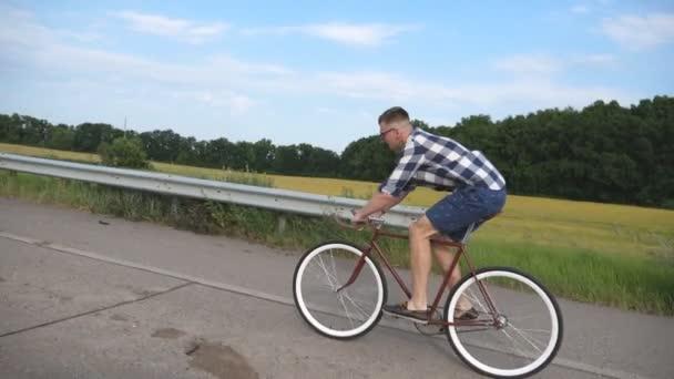 Fiatal jóképű férfi országút: vintage kerékpár lovaglás. Sportos srác a pálya-kerékpározás. Férfi kerékpáros, lovas rögzített halászfelszerelés bike autópálya. Egészséges aktív életmód lassú mozgás