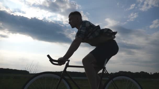 Silueta mladého muže jezdajícího na jízdních kolech s nádhernou oblohou slunce na pozadí. Sportovec na cestě na venkově. Cyklista na pevném rychlostním kole. Aktivní životní styl pomalý pohyb