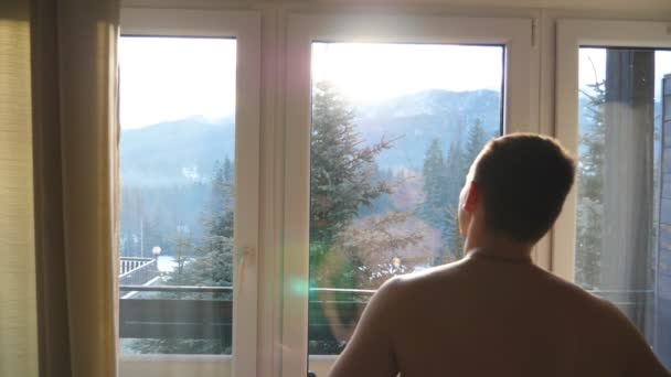 Nedaleko neidentifikovatelného atletického muže stojícího v ložnici hotelu a vyhlížel z okna za slunného dne. Pohledný mladík, který má krásnou krajinu brzy ráno. Pohled zezadu
