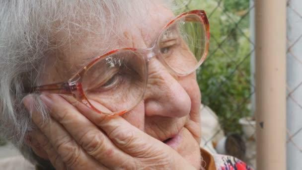 Portrét babičky s emocemi a pocity. Stařena se smutným výrazem ve venkovním prostoru. Babička se jí drží v obličeji a těžce vzdychala. Zavření zobrazení po straně pomalý pohyb