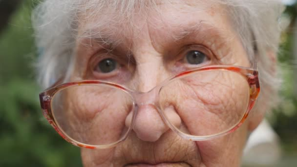 Old woman in glasses looking into camera outdoor. Portrait of sad grandmother with emotions and feelings. Granny wearing eyeglasses outside. Close up Slow motion