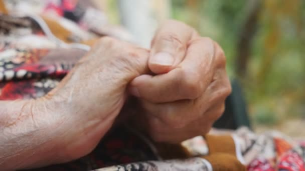 Grandmother making massage her wrinkle hands outside. Old woman taking care of her arms outdoor. Close up Side view Slow motion