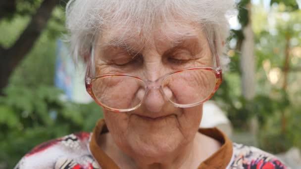 alte Frau mit Brille, die in die Kamera schaut und draußen lächelt. Porträt einer glücklichen Oma in Brille, die Zeit draußen verbringt. Gefühle der Großmutter. Zeitlupe in Nahaufnahme
