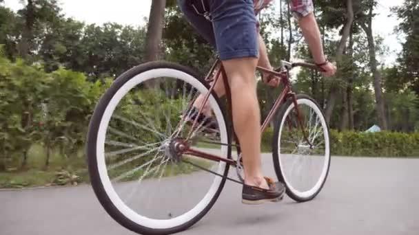 Mladý muž jezdí na veteránském kole v parku silnice. Sportovec na kole venku. Zdravý aktivní životní styl. Nízký úhel pohledu Zavřít Zpomalený pohyb