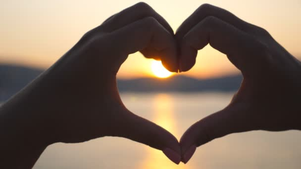Silhouette of young female hands making heart shape over sea background with beautiful sunset. Concept of summer vacation. Close up Slow motion