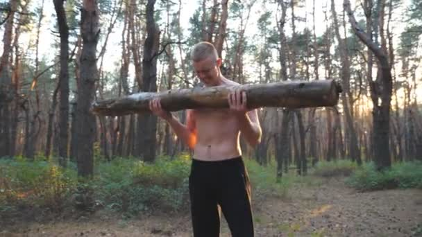Muscular man lifting hard weight training biceps. Strong and hardy guy working out outdoor. Athlete exercising in nature using big log. Concept of sport and active lifestyle. Dolly shot Close up