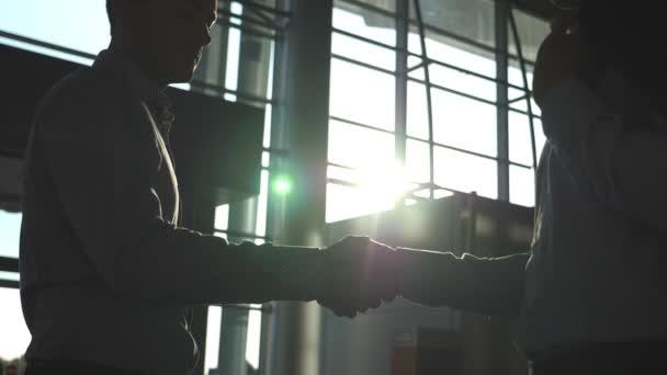 Dva bělošští obchodníci se vítají v úřadu. Kolegové se setkávají a potřásají si rukama v pozadí města. Potřesení rukou uvnitř. Třesení mužských paží uvnitř. Zavřít Zpomalený pohyb