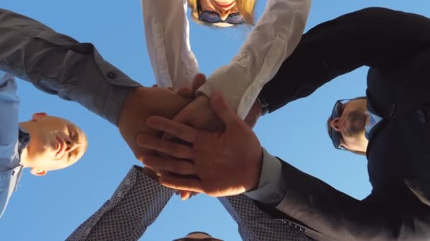 Group of young businessman stand in a circle and puts their hands together. Business people celebrate successful event. Concept of success team work. Bottom view Slow motion Close up