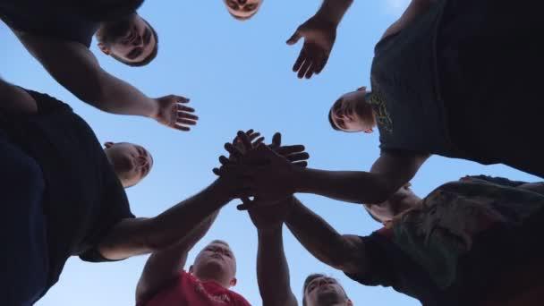 Mladí sportovci skládají ruce jeden po druhém v jednotě. Skupina nejlepších přátel položila ruce doprostřed kruhu a zvedla je k modré obloze. Koncept přátelství a týmové práce