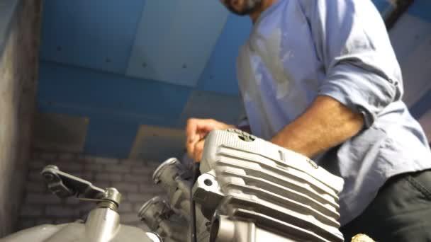 Vousatý mechanik opravující motor z nějakého vozidla. Auto master upevnění motocyklového motoru v garáži nebo dílně. Muž se zabývá servisem aut nebo motocyklů. Zavřít Pomalý pohyb Nízký pohled