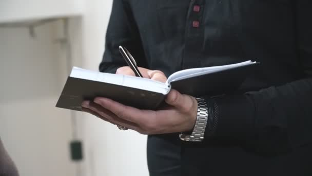 Professional journalist interviewing and writing text to notebook. Man keep diary. Unrecognizable student in black shirt writing notes on lecture. Concept of education. Slow motion Close up