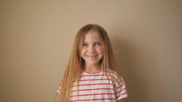 Malá usměvavá holka s blonďatými vlasy hledící do kamery. Zavřít emoce krásného dítěte s veselým výrazem ve tváři. Portrét šťastného ženského dítěte na pozadí zdi