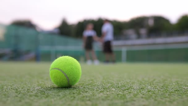 Close-up of the ball lying on the tennis court and the couple leaves court after playing tennis on a blurred background