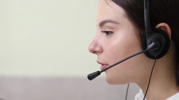 A girl receives a call from a client. A call center operator talks on the phone using a headset