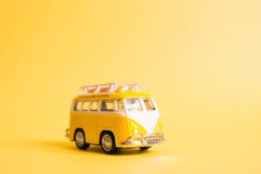 Funny yellow retro car with surfboard on yellow background