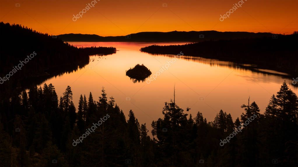 View of Lake Tahoe from near Emerald Bay, California, USA, including Fannette Island, on the sunrise in a summer morning, featuring a colorful, orange sky