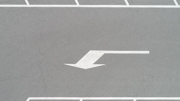 video of White painted arrow on asphalt road at parking