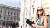 Fotografie Pretty teenager tourist with  travel guide visiting city Milan, Italy