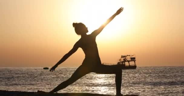 Mladá žena v body cvičení jógy na pláži výše.