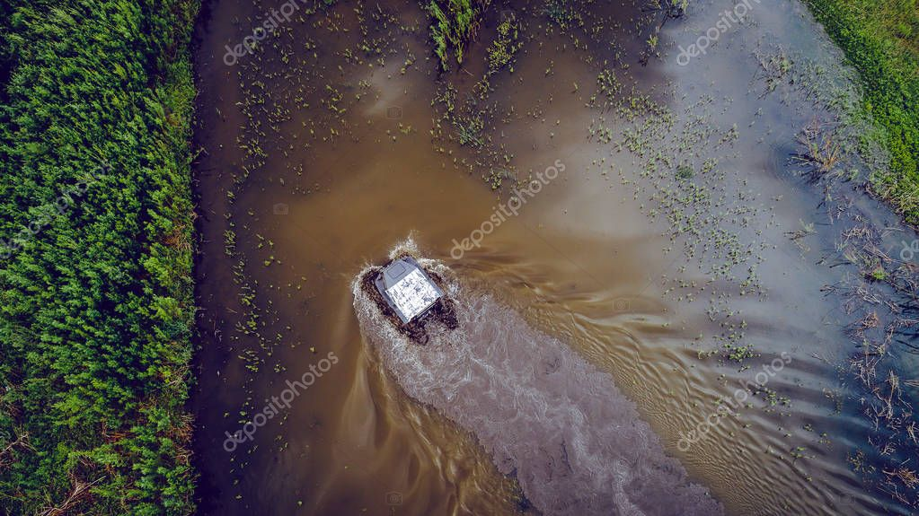 An off-road vehicle sails on the river. aerial above view top