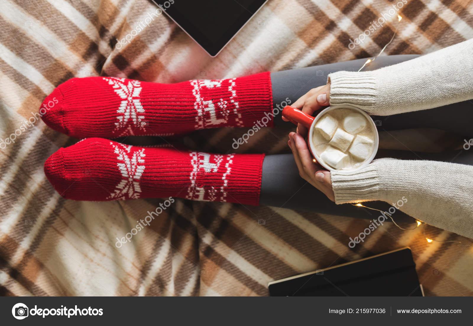 be439f842434 Γυναικεία χέρια και τα πόδια σε πουλόβερ και μάλλινων ζεστό κόκκινο κάλτσες  εκμετάλλευση ζεστό φλιτζάνι καφέ με το marshmallow