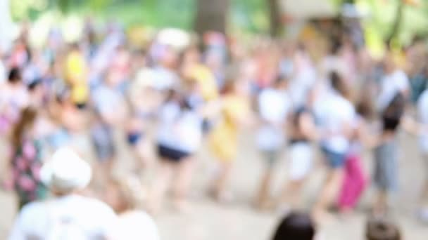 Summer party outdoors. Blurred background with dancing people in colorful clothes in forest, park, outdoors. Unrecognizable faces.