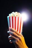 Fotografie ruce drží box s popcorn nad kino světlé pozadí, film koncepce