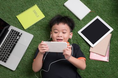 Cute little boy listens to music on the grass with his laptop, tablet and notebooks around.