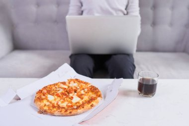 Man eating pizza having a takeaway at home relaxing resting