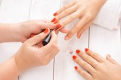 Žena stále nehty manikúra. Manikérka používaný Červený lak na nehty pro odběratele