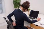 Podnikatelka, trpící bolesti zad a pasu v kanceláři