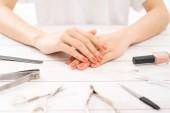 Péče o nehty a manikúra. Krásné ženské ruce s laky na nehty. Červená manikúra