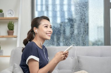 Happy young asian woman in earphones messaging on smartphone at home. Listening to music, sitting comfortably on gray sofa
