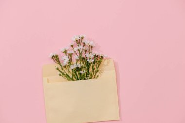 Opened envelope with flowers arrangements on pink background, top view. Festive greeting concept