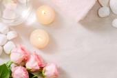 Růžový květ, esenciální olej, Dřevěný tác s čisté ručníky a osvětlení svíčky v lázních
