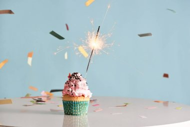 Single sparkler on cupcake on blue background