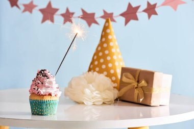 Birthday party background with cupcake, sparkler, party hat and present