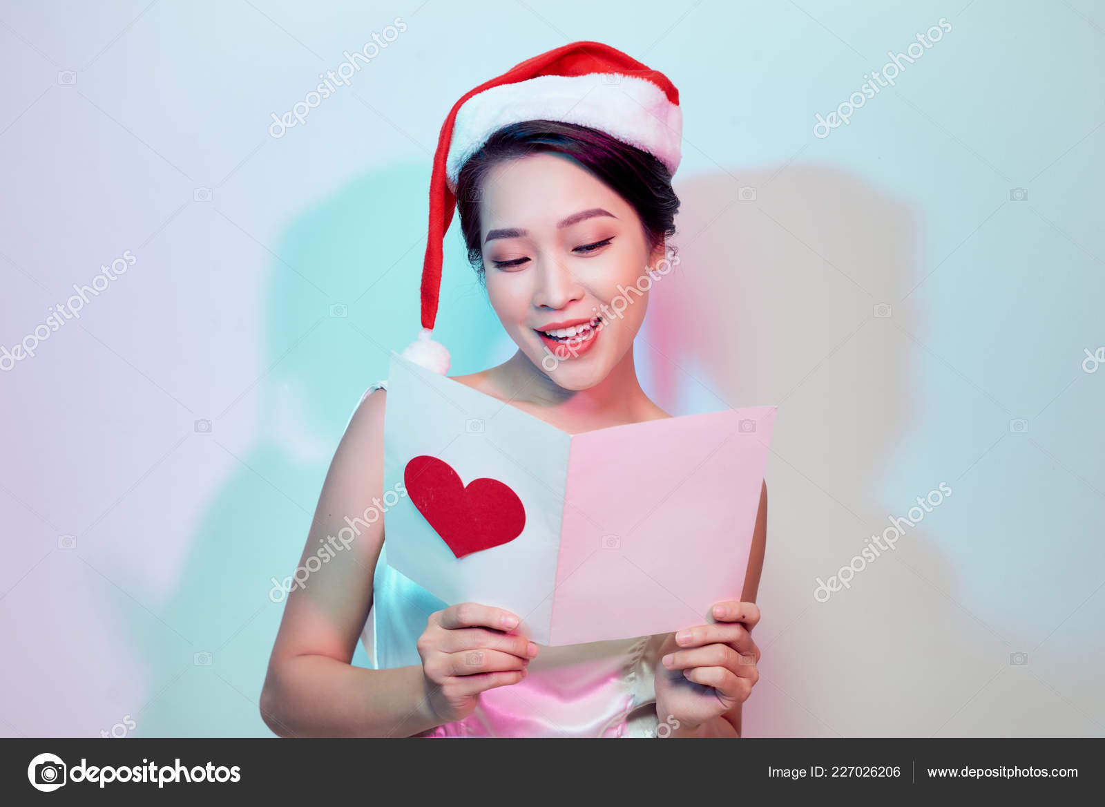 Beautiful young woman in santa hat holding postcard with red heart on light  background — Photo by makidotvn 086a4ba4e77
