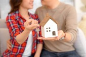 Happy couple holding keys to new house miniature