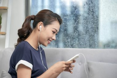 Happy young asian woman in earphones messaging on smartphone at window