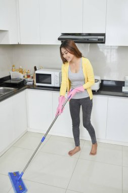 Housekeeping and cleaning concept, Happy young woman in pink rubber gloves wiping dust using mop while cleaning on floor at home.