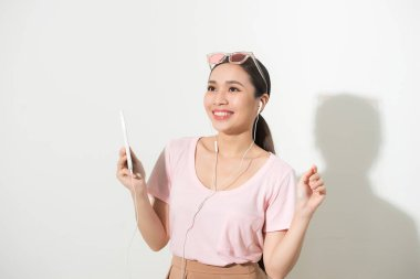 Portrait of a happy woman listening music in headphones and dancing isolated on a white background