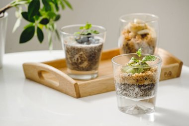 Fruits yogurt parfait with granola and chia seeds for healthy breakfast on wooden table