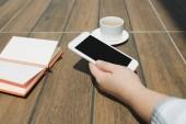Attrappe der Hände hält weißes Handy mit leerem schwarzen Desktop-Bildschirm mit Notizbuch und Kaffeetasse auf Holztisch im Café