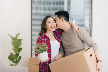 Young asian couple moving to a new apartment together relocation