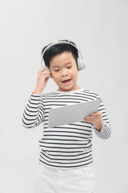 Little boy listening to music from his tablet on his headphones.