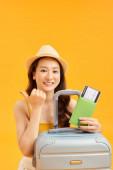 koncepce cestování. šťastná žena dívka s kufrem a cestovním pasem na oranžovém pozadí