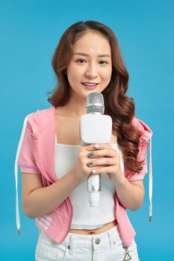 Young pretty woman happy and motivated, singing a song with a microphone,