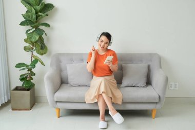 Young woman listening to music wearing headphones sitting on a sofa in the living room in a house interior